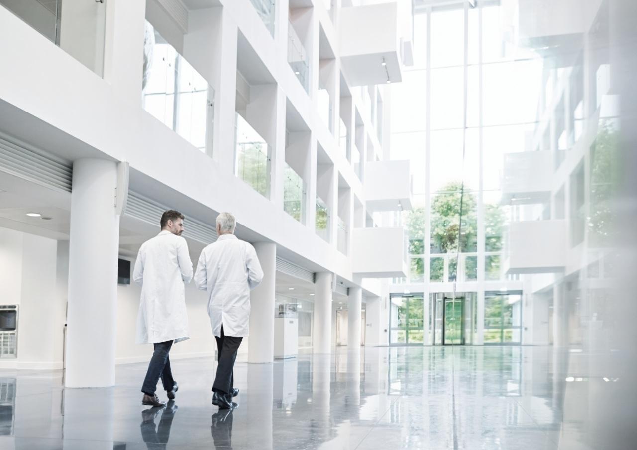 two male doctors walking in a hospital hallway
