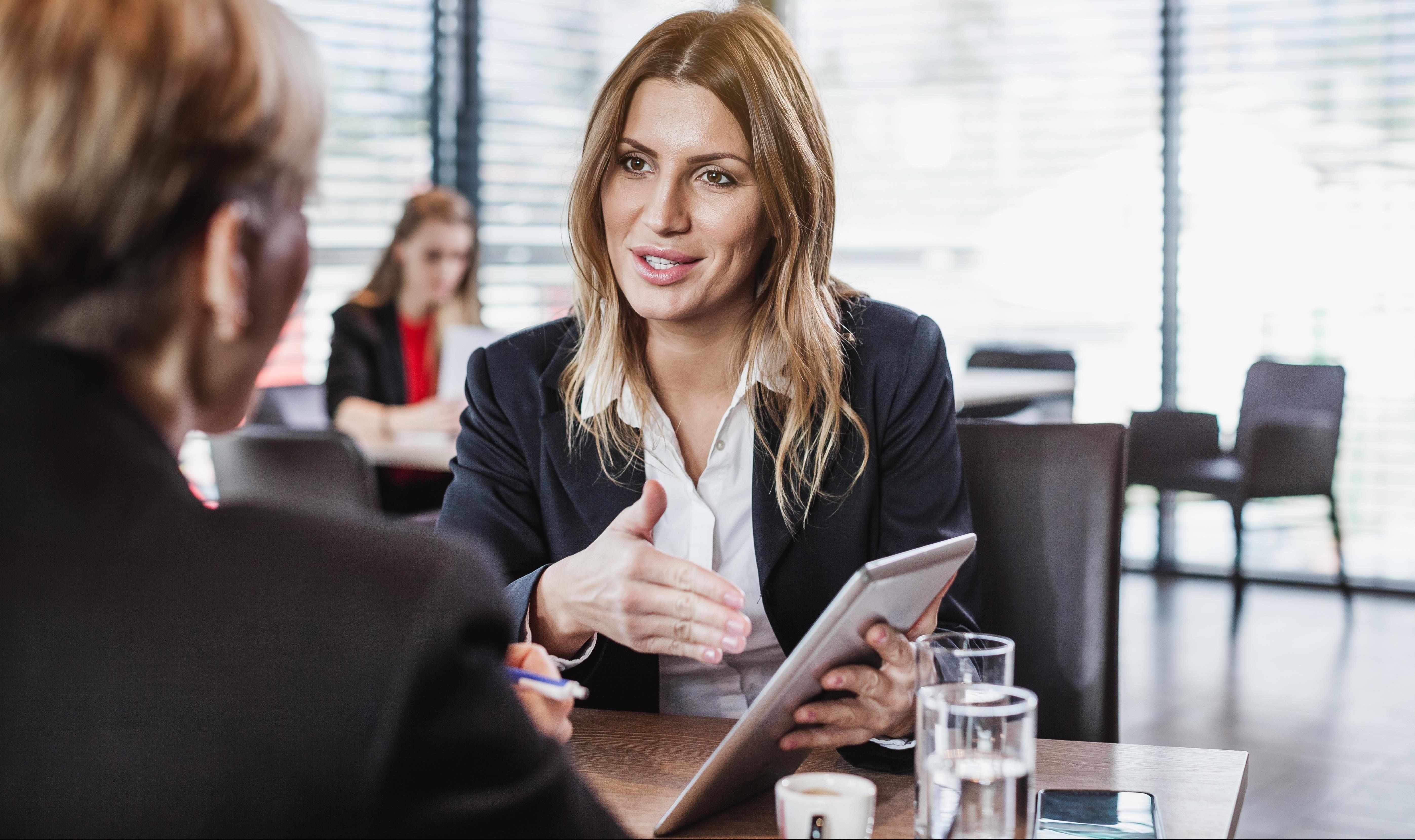 Zwei Geschäftsfrauen unterhalten sich in einem Cafe
