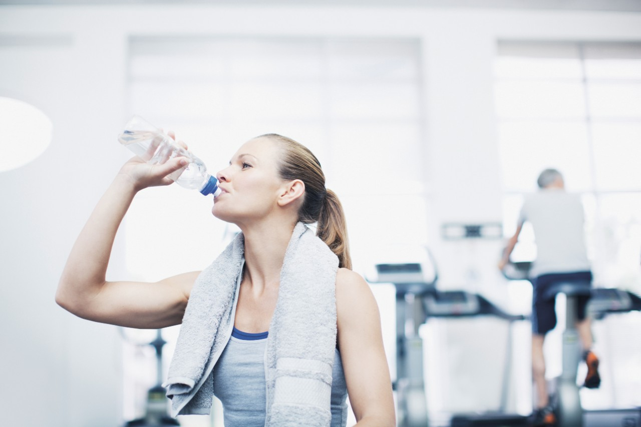 a girl drinking bottled water in a gym