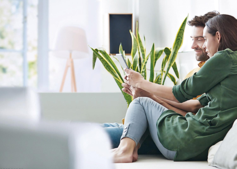 giovane coppia di ragazzi sul divano che guardano lo schermo di un tablet