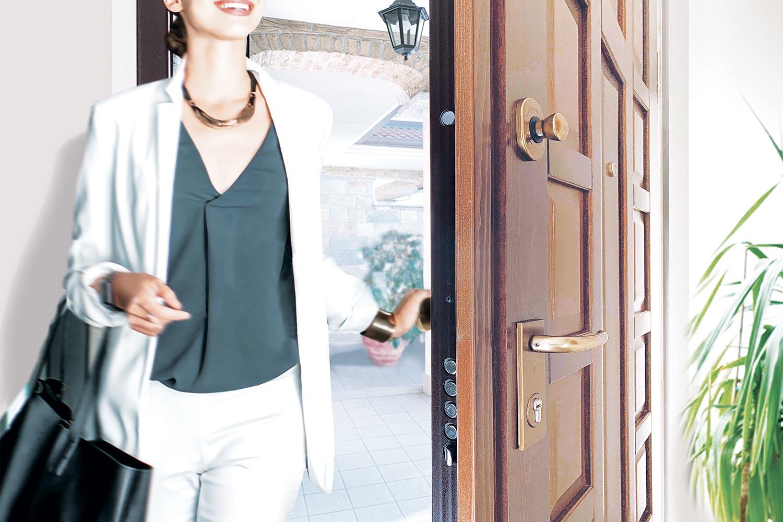 donna che entra in casa aprendo la porta blindata protetta da una serratura di sicurezza CR