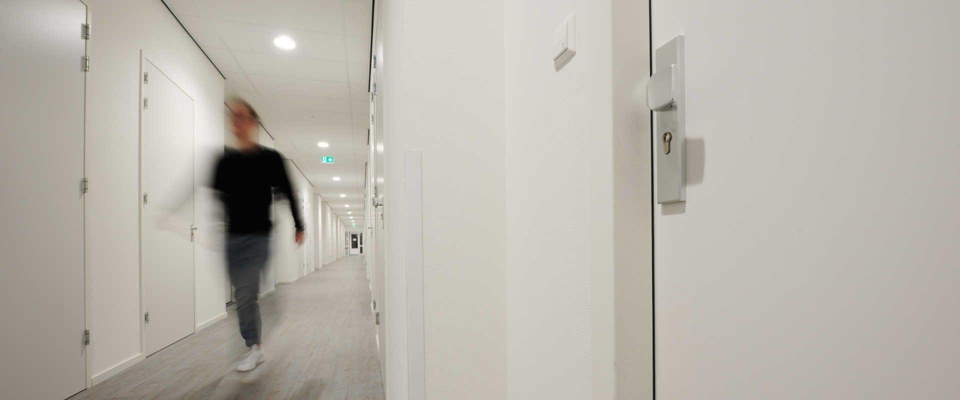 man walking through a hallway, focus on a door