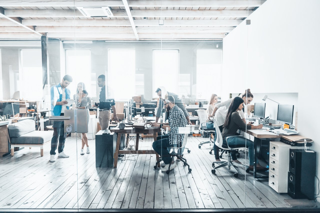 a group of people working in an open space workspace